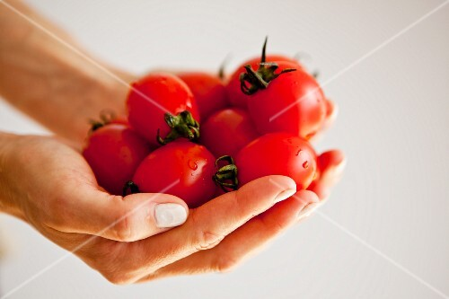 A woman holding fresh tomatoes