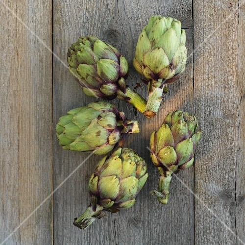 Five artichokes on a wooden surface