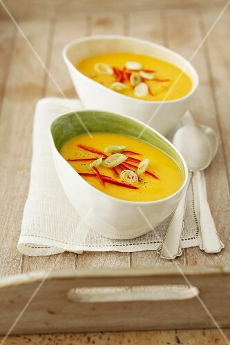 Cream of pumpkin soup with chilli strips and spring onions
