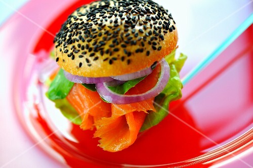 A poppyseed roll filled with salmon, onions and salad