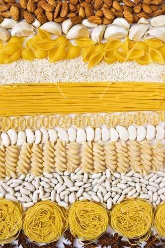 Almonds, garlic, rice, pasta and beans in rows