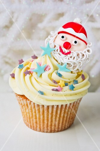 A vanilla cupcake decorated with a Father Christmas and sugar stars