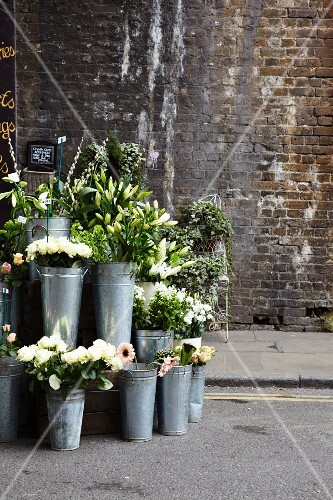 A flower stall with zinc vases in front of an old brick wall