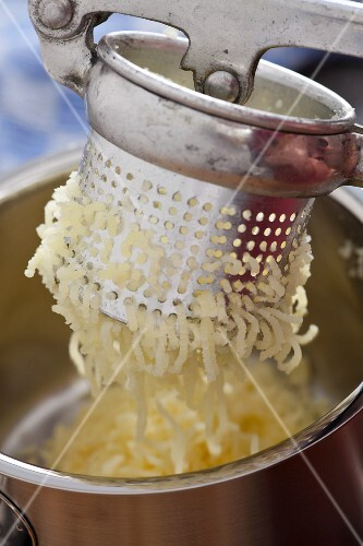 Potatoes being put through a potato ricer