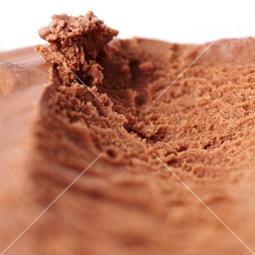 Traces left by an ice cream scoop in a container of homemade chocolate ice cream