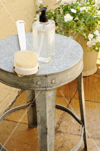 Shower gel and a back brush on a zinc stool beneath the garden shower