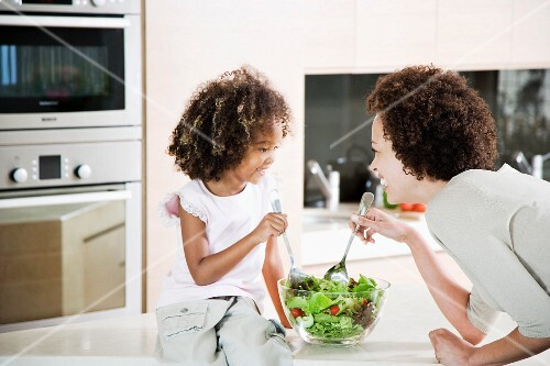 Mother and young daughter preparing healthy salad lunch together