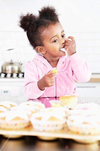 A little girl eating frosting from cupcakes