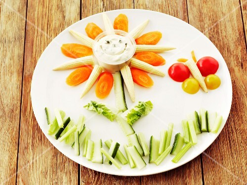Raw vegetables (cucumbers, carrots, baby corn cobs and tomatoes) and a herb quark dip arranged as a flower and a butterfly on a plate