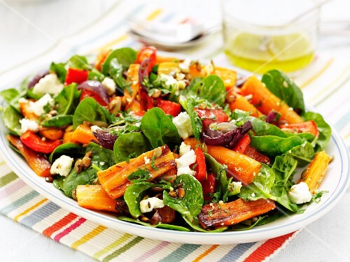 A colourful plate of salad with roasted carrots, dried tomatoes, red peppers, sheep's cheese, spinach, herbs and nuts