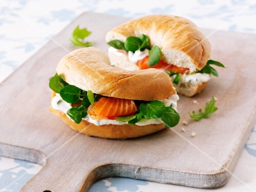 Cream cheese, bittercress and smoked salmon bagel on a chopping board