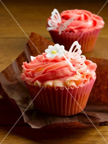 Cupcakes decorated with strawberry cream, butterflies and sugar flowers