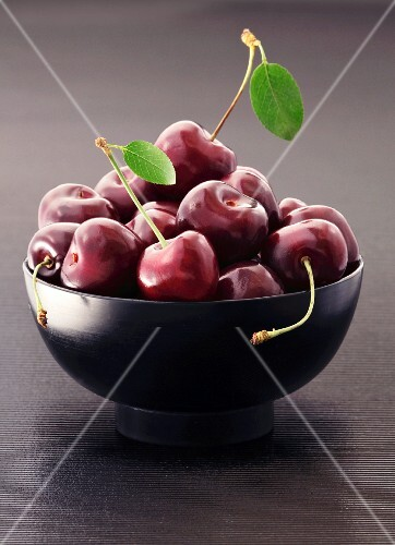Fresh cherries in a black bowl