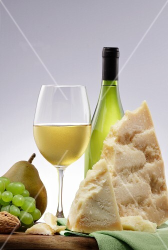An arrangement of white wine, cheese, fruit and nuts
