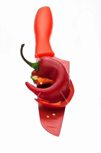 Half a red chilli pepper on a red knife