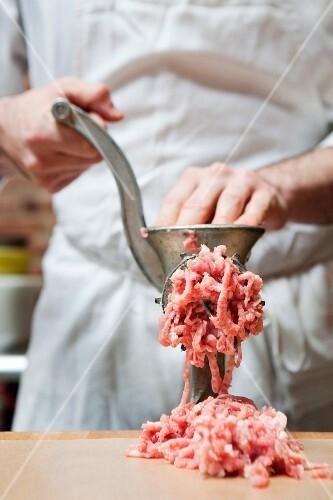 Butcher making mince
