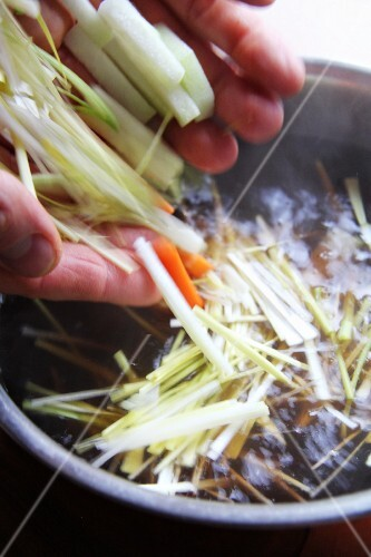 Hands adding julienned vegetables to a pot of hot water