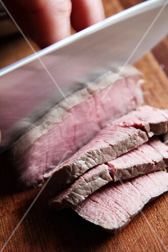 Sliced beef fillet with a chef's knife