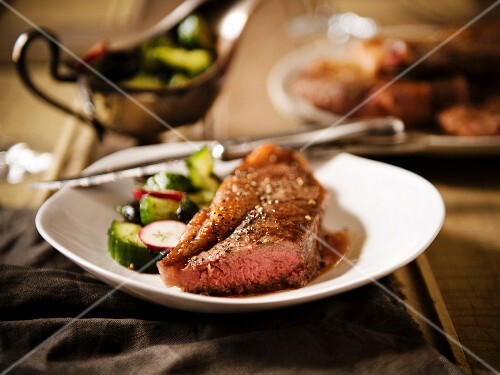 New York Strip Steak with Salad on a White Plate