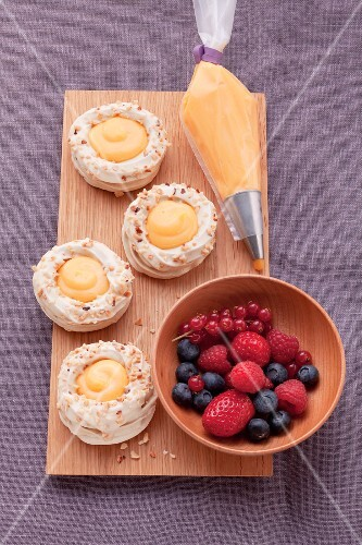 A board with four meringue nests filled with orange cream, next to a piping bag of orange cream and a bowl of fresh berries