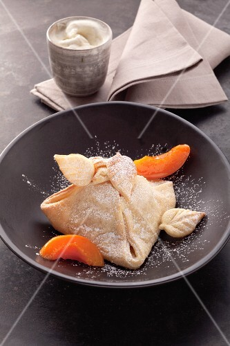 Apricot parcels with apricot pieces and icing sugar in a black dish