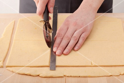 Squares of dough being cut out with a rule and a pizza wheel