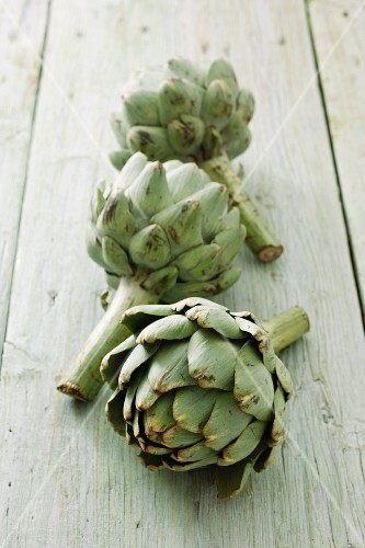 Three artichokes on a wooden surface