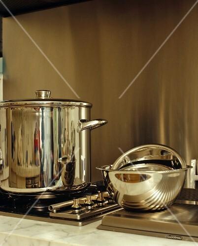 Stainless steel pan on hob and chrome mixing bowls