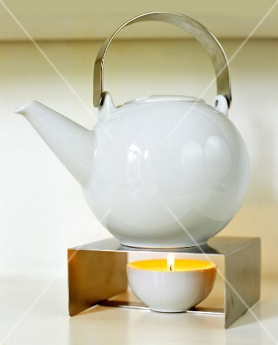 Lit candle under teapot on metal stand