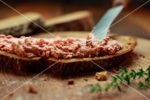 Liver sausage being spread onto a slice of bread