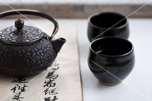 A teapot and two black tea bowls