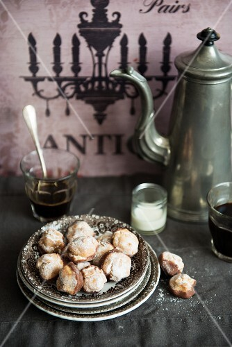 Orange amaretti on a stack of plates against a rustic background with a coffee pot