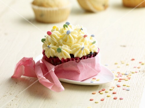 A cupcake decorated with cream and sugar sprinkles