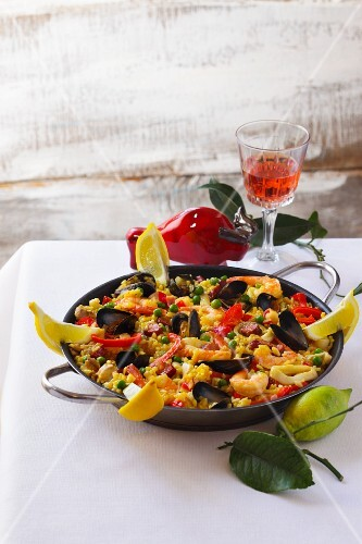 A pan of mixed paella and a glass of wine