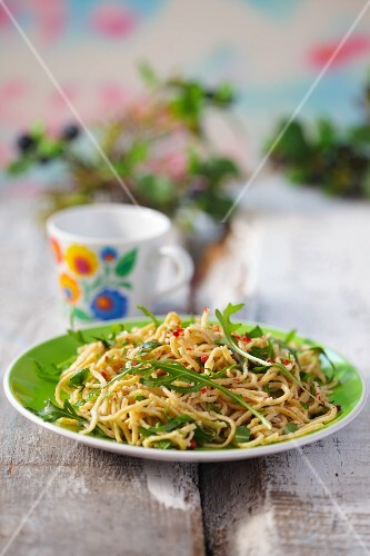 Homemade pasta with rocket on a green plate