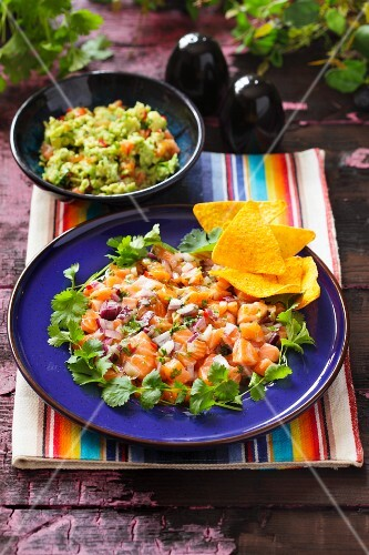 Ceviche as a main course on a blue plate with coriander and tortilla chips and a bowl of guacamole in the background