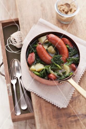 Grünkohleintopf mit Pinkelwurst, in einem Stieltopf; Aufsicht