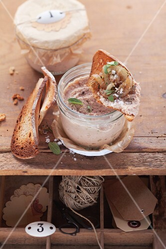 Streichwurst in einem Schraubglas, daneben und darauf geröstete Brotscheiben