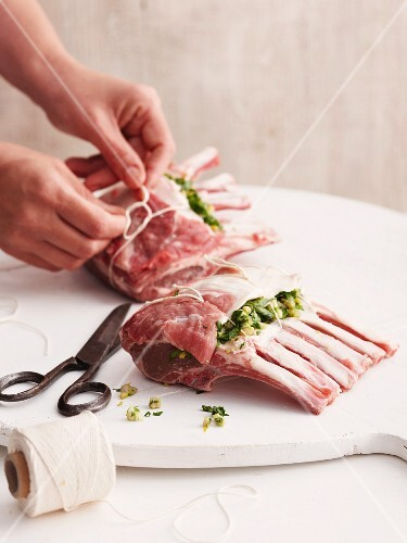 Stuffed lamb loin rack joints being tied with twine