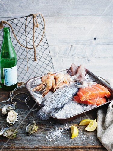 Fish and seafood in a roasting dish with ice on a rustic wooden table