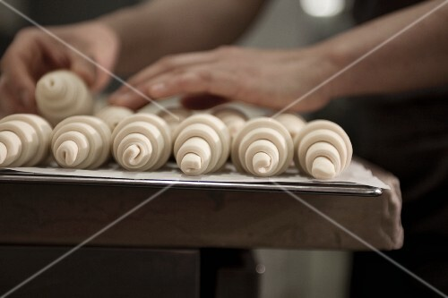 Hands sorting unbaked croissants
