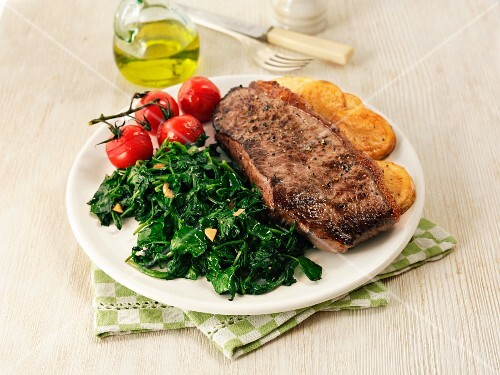 Beef steak with spinach, tomatoes and potatoes