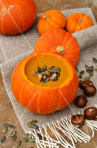 Pumpkin soup with chestnuts and pumpkin seed in a hollowed-out pumpkin