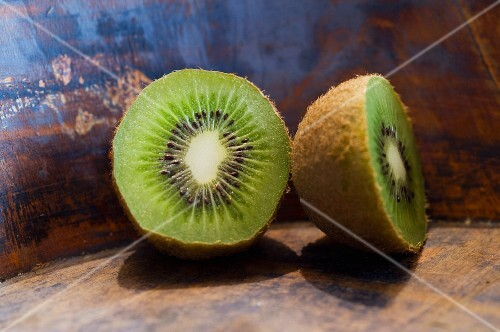A halved kiwi on a wooden surface