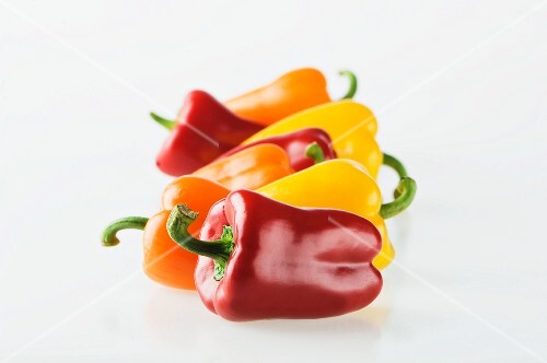 A row of red, yellow and orange peppers