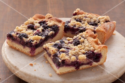 Three slices of blueberry crumble cake on a stone platter