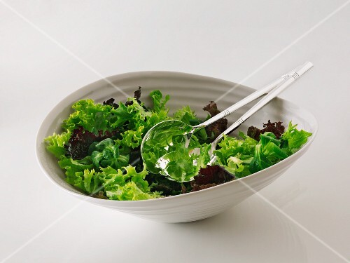 Mixed lettuce in a bowl with salad servers