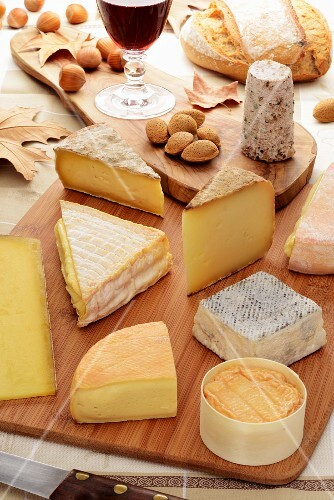 Various types of cheese, nuts, bread and red wine