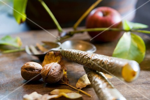 An arrangement of walnuts and cutlery with an apple in the background