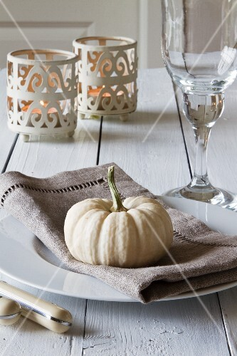 An autumnal place setting with an ornamental squash, tealight holders and a wine glass